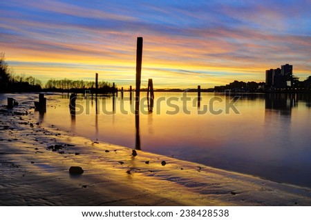 sunset glow over the river and beach, with smooth water surface