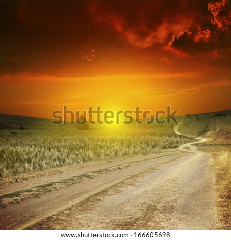 sunset green field and road - stock photo