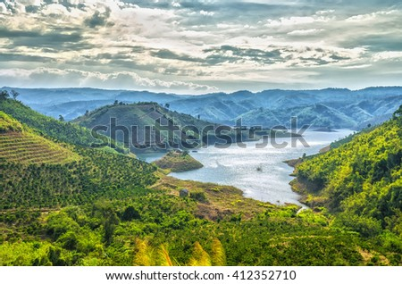 Sunset hillside Ta Dung hydro lake with mountains blue swirled large lake with islands, far away from the real little house idyllic rural countryside scene Vietnam - stock photo