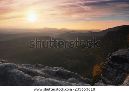 Sunset in a beautiful rocky park  Bohemian-Saxony Switzerland. Sandstone peaks and hills increased from foggy background, the fog is orange due to sun rays.