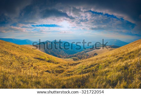 Sunset in a Carpathian mountains with colorful dramatic sky and yellow autumn grass on a meadow - stock photo