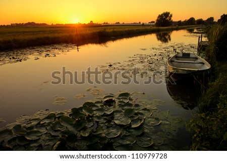 Sunset in a landscape in rural Holland with a ditch, an old boat and a bunch of waterlily. - stock photo