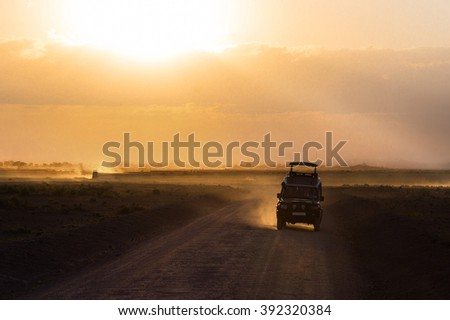 Sunset in african savannah, silhouettes of safari car and animals, Africa, Kenya, Amboseli national park  - stock photo