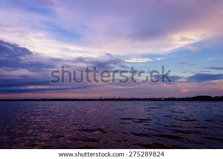 Sunset in Arkhangelsk port view from the opposite bank of the river Northern Dvina. Russia