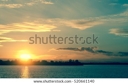 sunset in autumn in November, a bright yellow, brown and black colors, to sit round the sun, clouds heavy different sizes,sun on the horizon,  solar path the pond, azure hue
