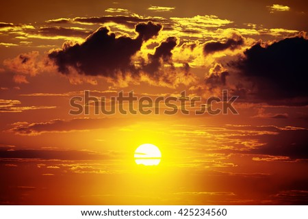 sunset in beautiful sky with clouds as background, dark red color - stock photo