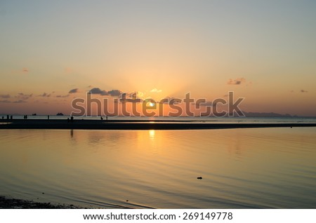 Sunset in clouds on the sea beach - stock photo