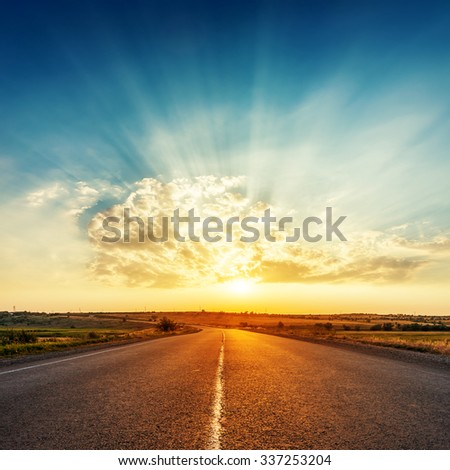 sunset in clouds with sunrays over road to horizon - stock photo
