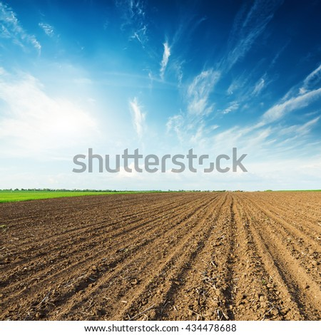 sunset in deep blue sky and black plowed field - stock photo