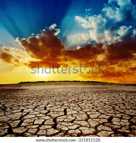 sunset in dramatic sky over desert - stock photo