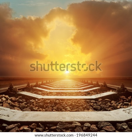 sunset in dramatic sky over railroad - stock photo
