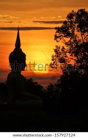 sunset in front of a Buddhist sculpture - stock photo