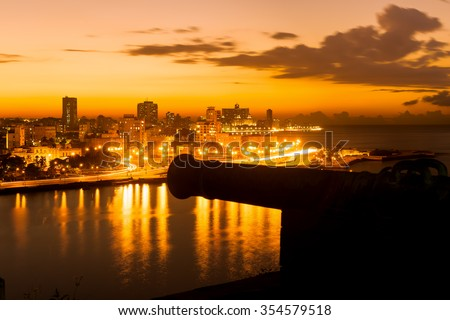 Sunset in Havana with a view of  the city skyline and an out of focus old spanish cannon on the foreground - stock photo