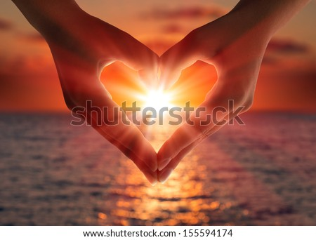 sunset in heart hands - stock photo