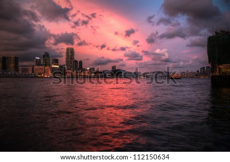 Sunset in Hong Kong: view of Victoria Harbour from Kowloon Island - stock photo