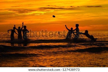 Sunset in January at Ft Meyers Beach in Florida.  A group of teens playing water football after sunset at Ft Meyers Beach in January.