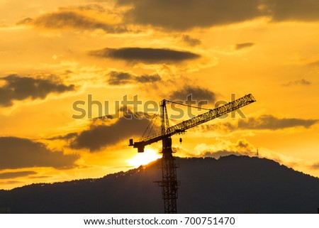 Sunset in mountain scene in front tower crane
