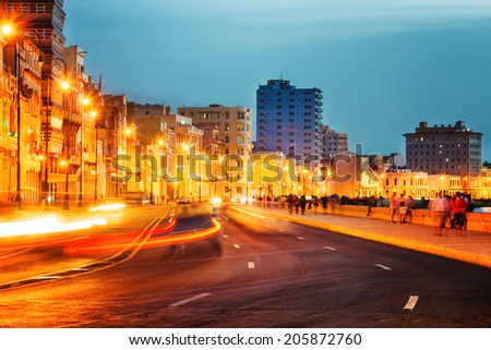 Sunset in Old Havana with  the street lights of El Malecon and light trails from the passing cars - stock photo