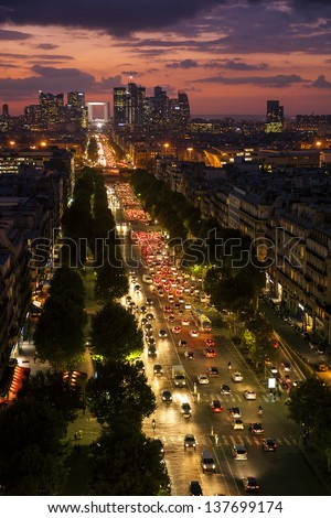 Sunset in Paris over The Champs Elysees, Etoile Charles De Gaulle and the skyline of La Defense - stock photo