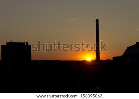 Sunset in Prague behind a tall factory chimney with sun right on the edge of the buildngs. Place: Holesovice area, Prague, Czech Republic