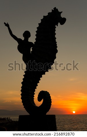 Sunset in Puerto Vallarta with the silhouette of a sea horse riding mermaid  in the foreground