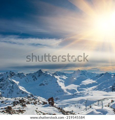 Sunset in snowy blue mountains with clouds. Winter ski resort - stock photo
