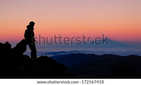 Sunset in Teide Volcano, Tenerife, hiker watching the shadow of the mountain, beautiful colors orange and blue.