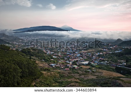 Sunset in Tenerife Island seen from Anaga massif; Las Mercedes agglomeration is in the valley, followed by San Cristobal de la Laguna, and El Teide mount is at background, Canary, Spain  - stock photo