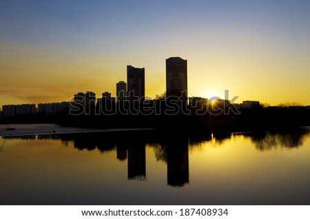 Sunset in the city, reflcting in smooth water. Picture taken in Strogino, Moscow, Russia.