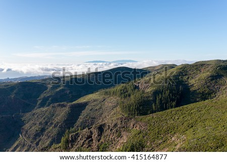 Sunset in the highlands of La Gomera. View direction Valle Gran Rey. In the background the Island La Palma. Clouds from trade winds over the mountains on La Gomera. The clouds comes from the Azores