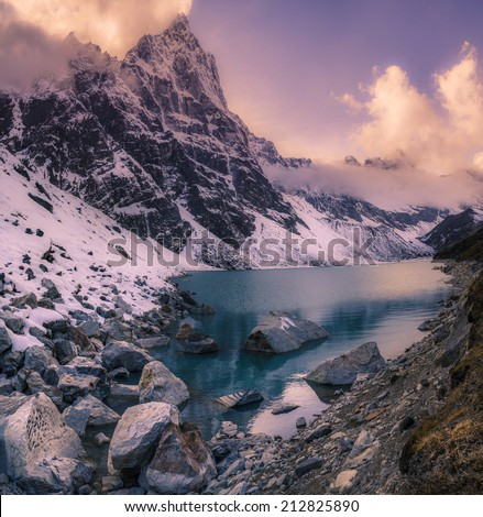 Sunset in the Himalayas mountains. Lake on the foreground. Trekking and alpinism - stock photo