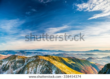 Sunset in the mountains. Landscape with hills, blue sky and clouds - stock photo