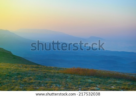 Sunset in the mountains. Sun and blue fog on background