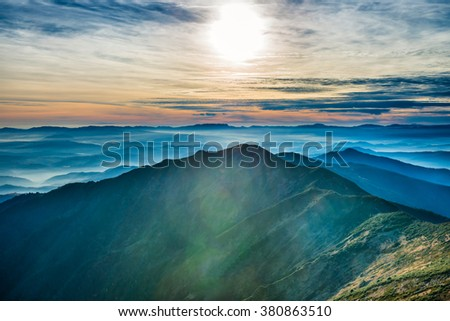 Sunset in the mountains. Sun and colorful clouds over blue hills