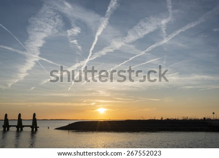 sunset in the northsea with lines from planes in the sky and wooden structure in the water