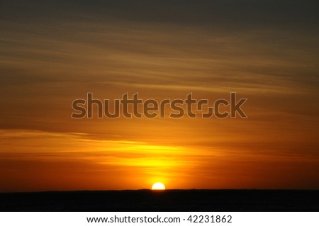 Sunset in the ocean with different colours in the sky - stock photo