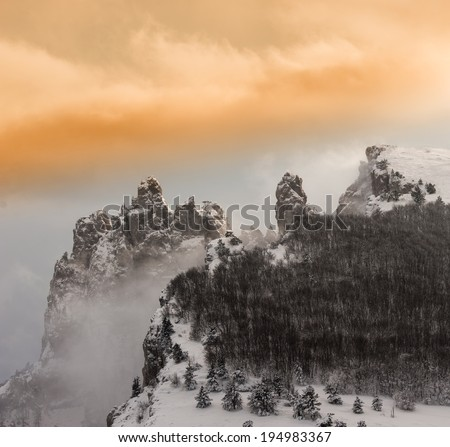 Sunset in the rugged mountains of clouds and snow, winter season