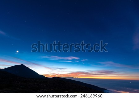 Sunset in the Teide National Park, Tenerife/Spain. On the left is the Vulcano Teide and on the right the Atlantic Ocean. The Moon is shining over the Vulcano. - stock photo