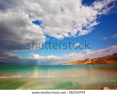Sunset. Incredible lighting effects on the Dead Sea in Israel. Clouds are reflected in the sea - stock photo