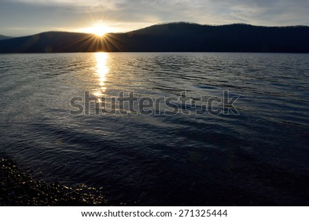 sunset into the Mountains at McDonald lake in Glacier National Park, Montana in summer - stock photo