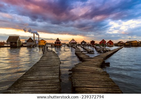 Sunset lake Bokod with pier and fishing wooden cottages, power plant in background, Hungary - stock photo