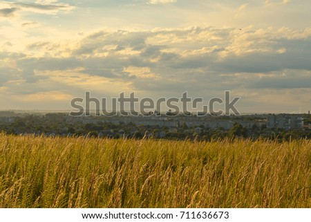 Sunset landscape. Beautiful sky, field and city.