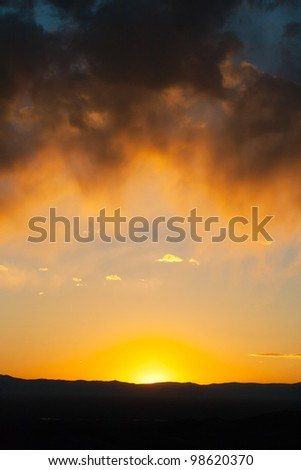 Sunset landscape with colorful frame of clouds - stock photo