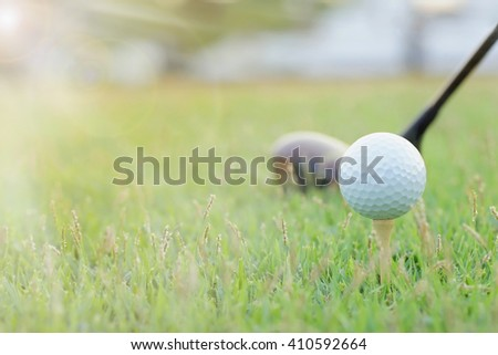 Sunset light at Golf ball on green grass. ( selective focus )With lens flare effect. - stock photo