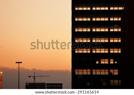 Sunset light going through dismantled office building. Skeleton of building completely naked. - stock photo