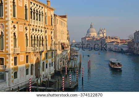 Sunset lights up the Venice Conservatory, overlooking the Grand Canal. In the distance the basilica of Santa Maria della Salute - stock photo