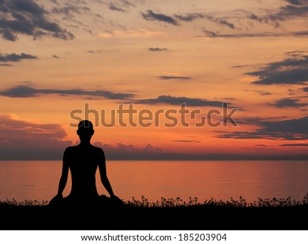 Sunset meditation. Silhouette of a woman doing yoga exercise in the evening.