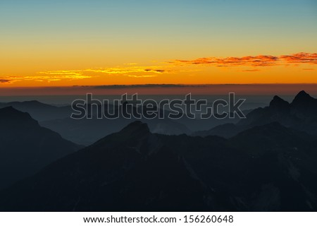 sunset mood in austrian mountains at orange cloudy sky - stock photo
