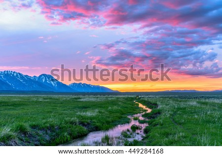 Sunset Mountain Meadow - Colorful spring sunset at a green mountain field with a winding stream near Mormon Row historic district in Grand Teton National Park, Wyoming, USA. - stock photo