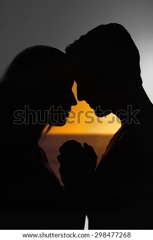 sunset of a beautiful day against silhouette of affectionate couple face to face holding hands - stock photo